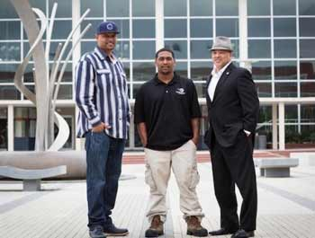 Three men standing in front of a glass building