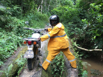 Health worker pushes a motorcycle over a tree bridge