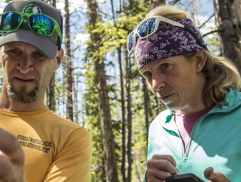 Two adventure scientists check and log data from a checkpoint in the woods