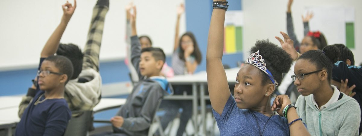 Students in a classroom raise their hands to answer a question