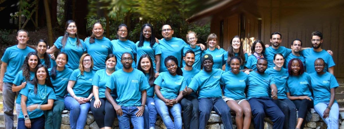 HEAL fellows wearing blue t-shirts sitting on a bench
