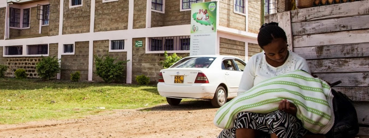 Woman sitting outside African hospital