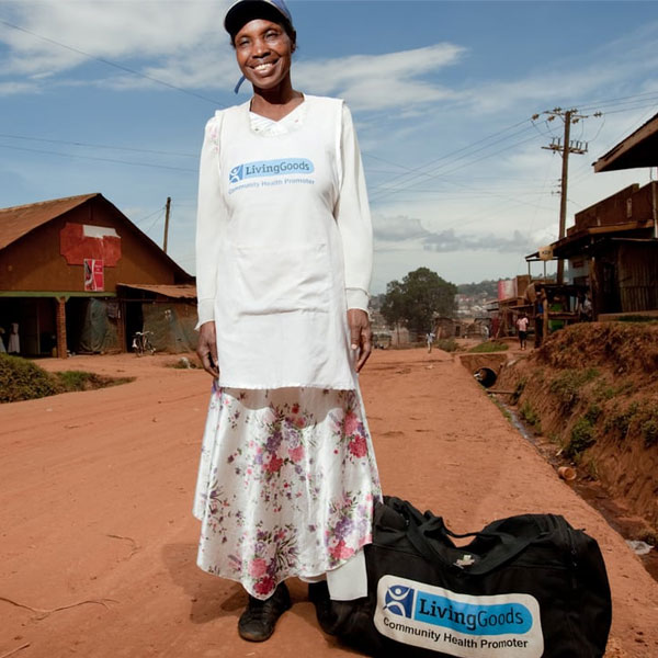 African woman stands smiling on a dirt path