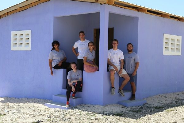 New Story team sitting on the steps of a home purple painted house that they built in Haiti