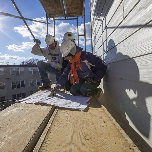 3 volunteers for Habitat for Humanity look at building plans