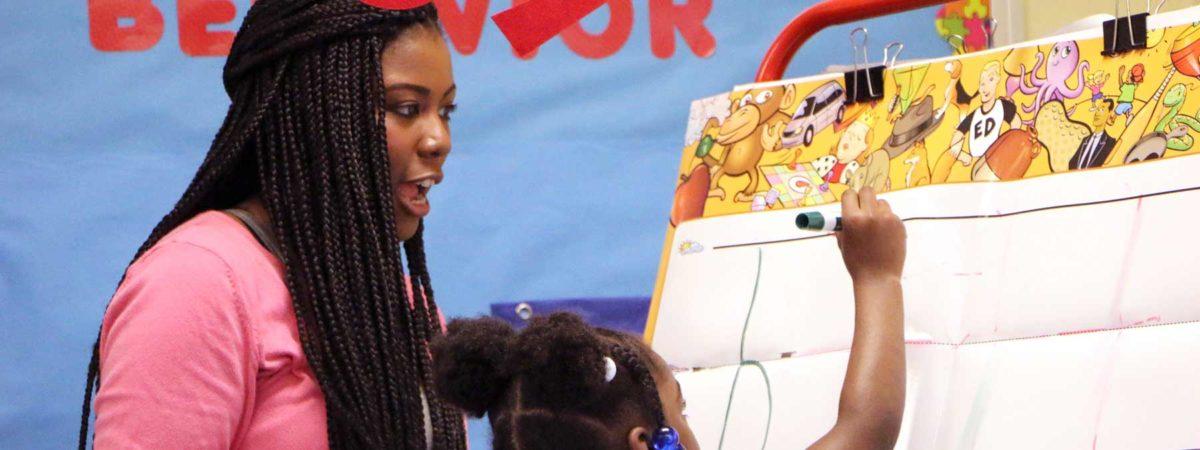 Woman teacher helping young girl