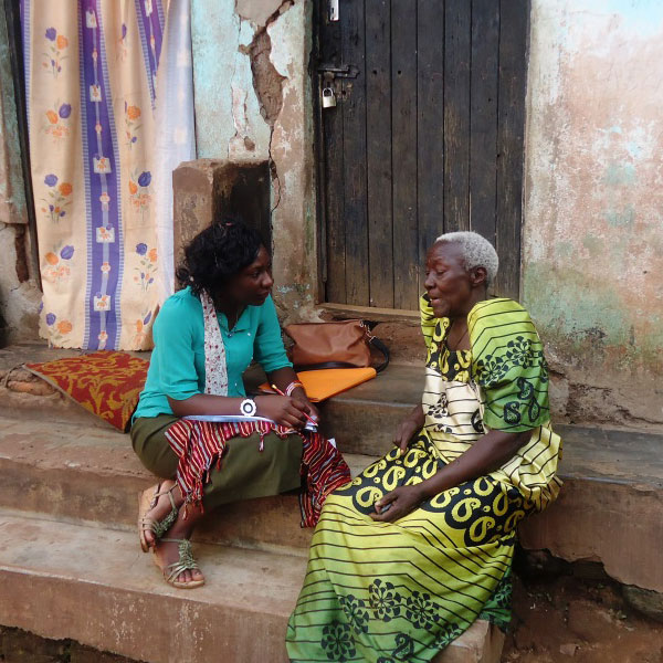 Two African women speaking on the steps of an African home