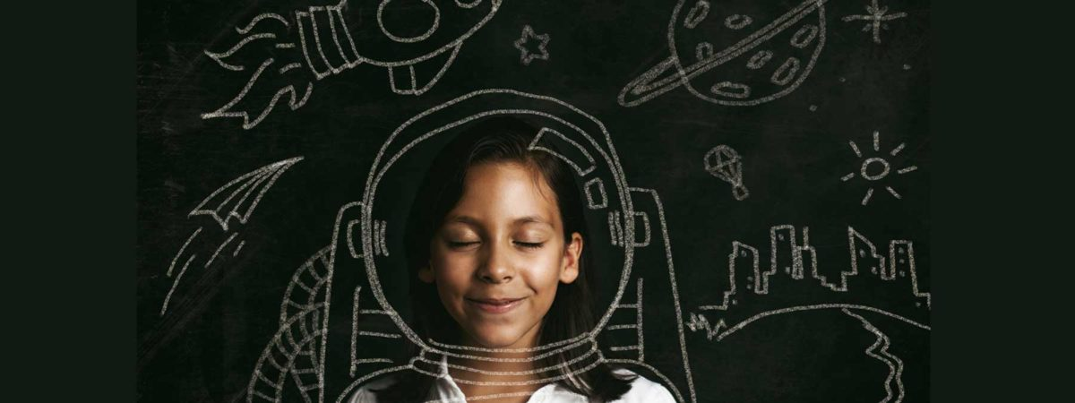 Little girl in front of a blackboard with an astronaut helmet drawn around her in chalk