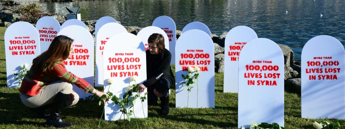 Grave stones that say 100,00 lives lost in Syria