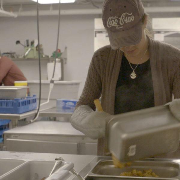 Student volunteer scoops food for homeless