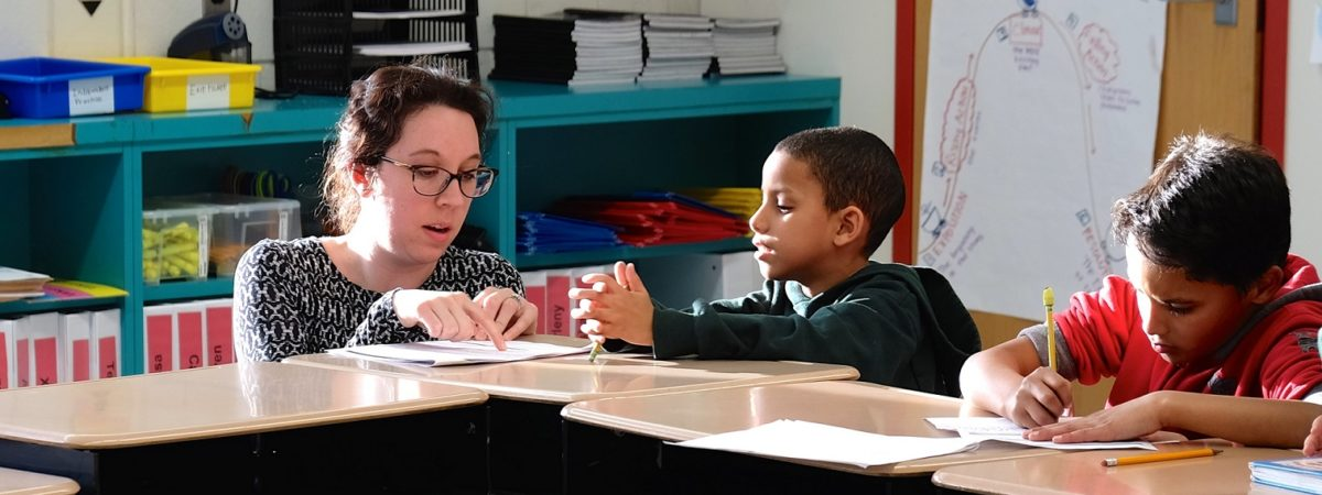 Teacher assists two young students at their desk