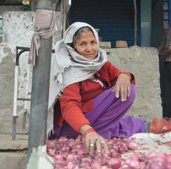 Woman in india crouched down by small red potatoes