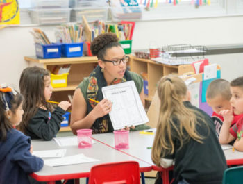 Female teacher in a classroom sits at a table with students