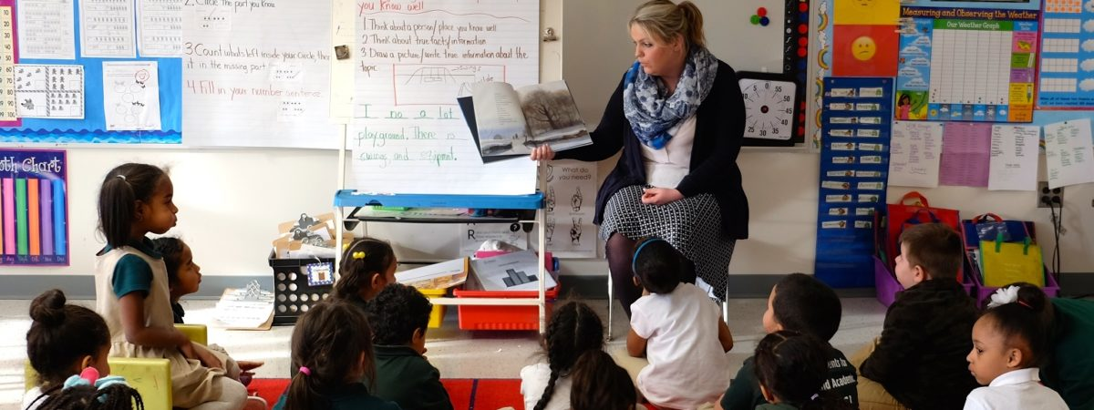 Female teacher reads a book to a classroom full of children