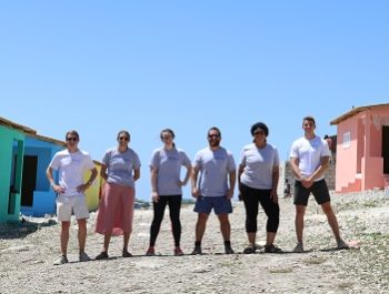 New Story team standing in between a row of homes they built in Haiti