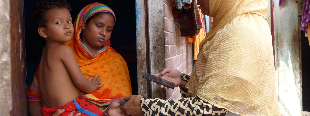Indian woman holding a baby in a doorway has finger printed by another Indian woman
