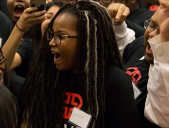 Young woman cheers while wearing a Braven t-shirt
