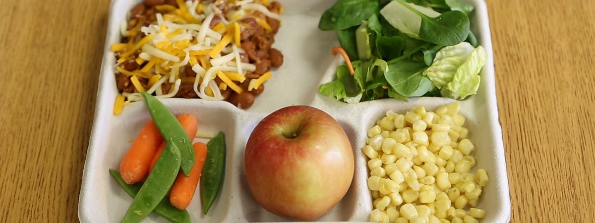 Picture of a school lunch tray featuring an apple. corn, salad, chili and green beans