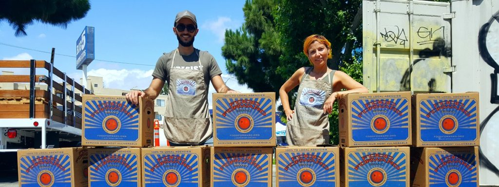 Two food forward farmers stand among towering boxes filled with produce