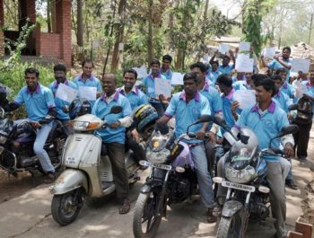 A large group of Indian motorcyclists gather and smile
