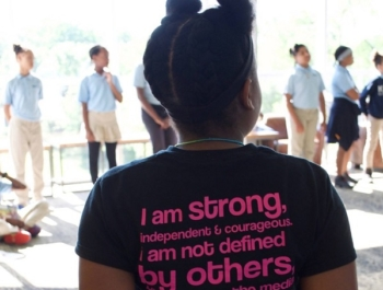 Young black girl stands with her back to the camera wearing an inspiring t-shirt with a message that