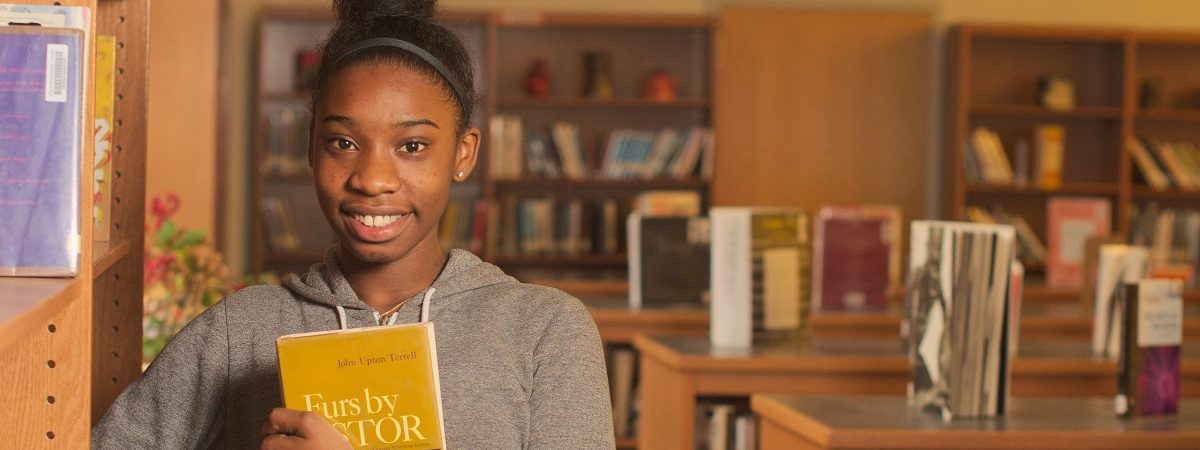 A young african american student holds a book in a library