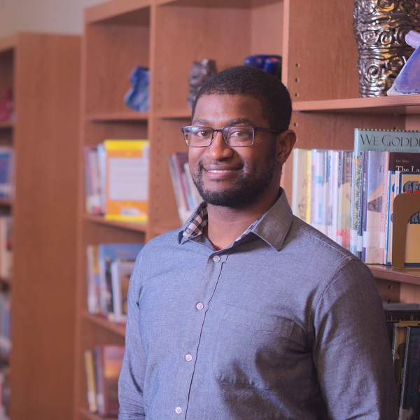 An african american man stands smiling in a library