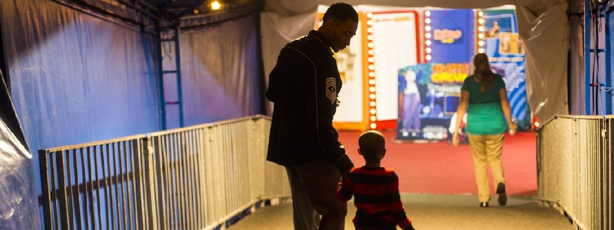 Father and son walk down the halfway smiling at one another. Bright lights fill the circus like room.