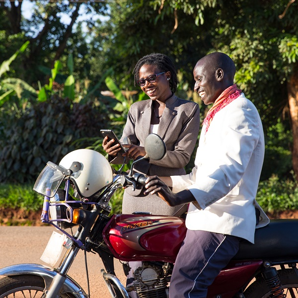 Maureen Nuwamanya demonstrates to boda boda rider Tumwebaze Sam how he can access free legal advice from Barefoot Law through a cell phone.