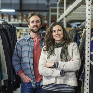 Co-founders of The Renewal Workshop, Jeff Denby and Nicole Basset, stand in the middle of their showroom smiling