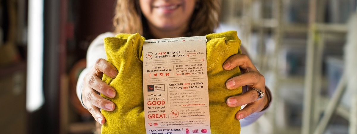 A woman holds out a yellow sweater in packaging that explains that the sweater has been repaired by The Renewal Workshop