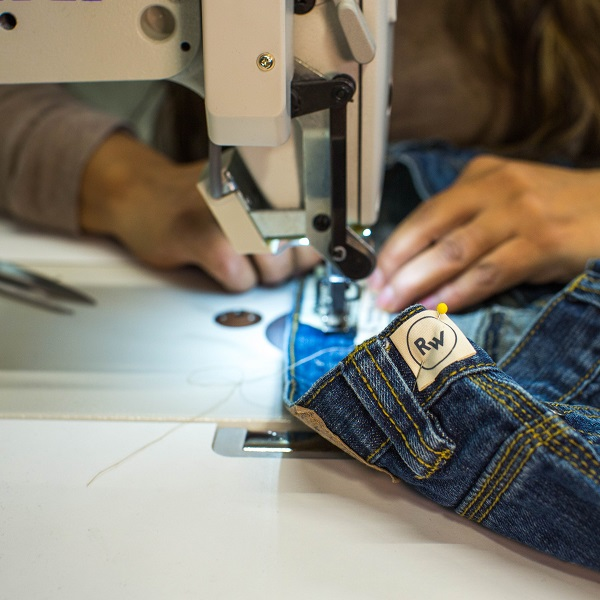 A pair of blue jeans are run through a sewing machine. The label on the jeans read
