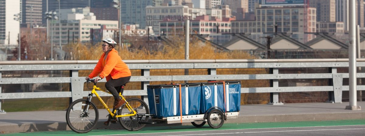 A female Wash Cycle Laundry employee riders her bike pulling a cart of laundry with the Philadelphia city scape in the background