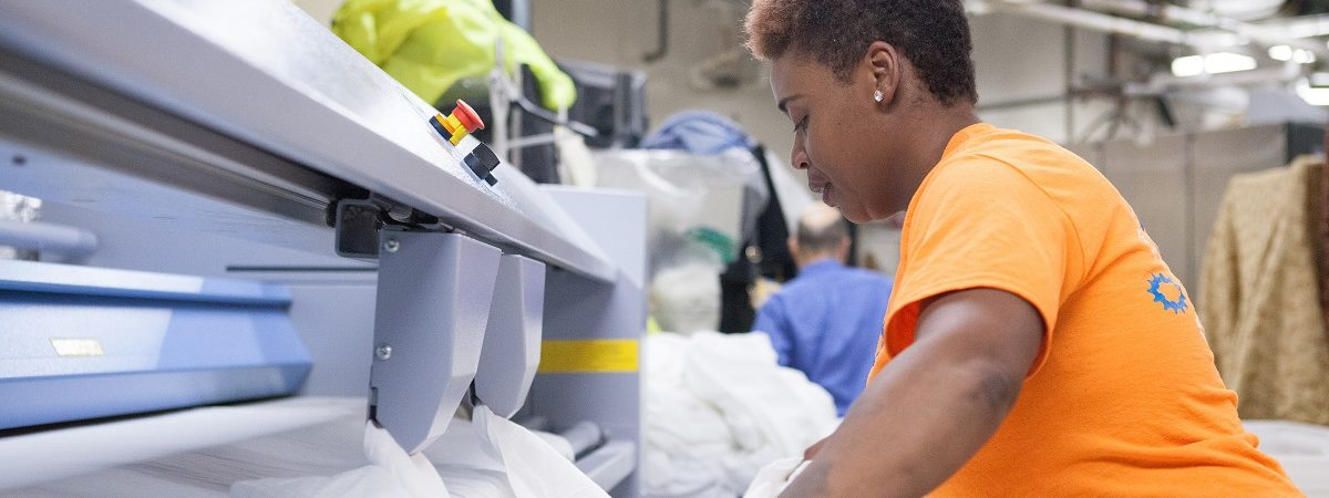A female Wash Cycle employee folds laundry