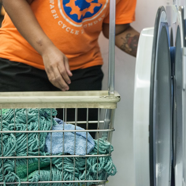 A Wash Cycle employee loads laundry into an industrial washing machine