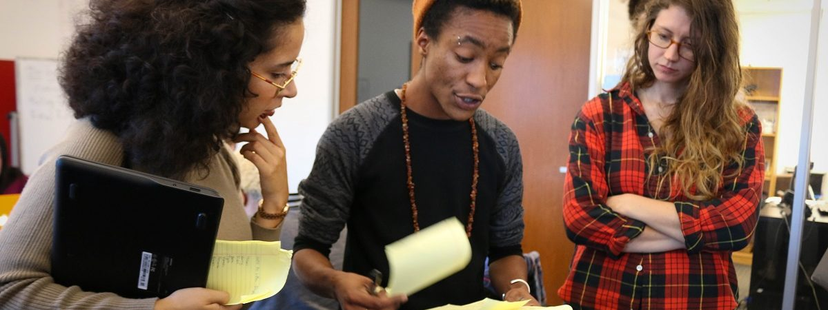 Three Vote.org staff members flip through pages of yellow notes while discussing voter turnout