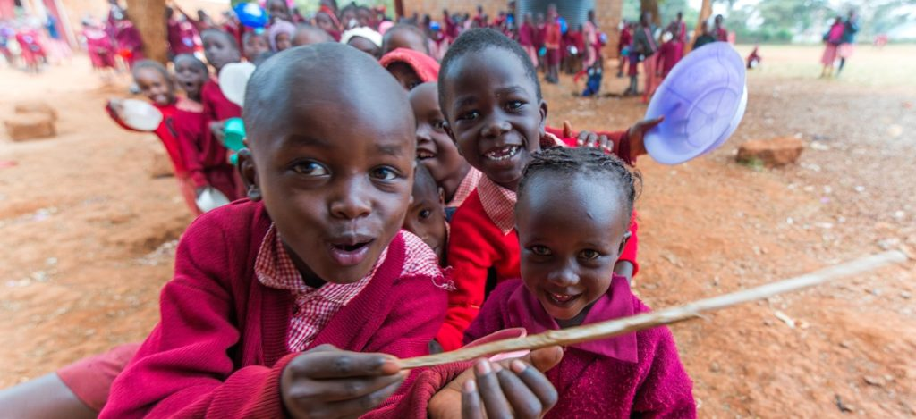 Happy African school children smile and play with utensils