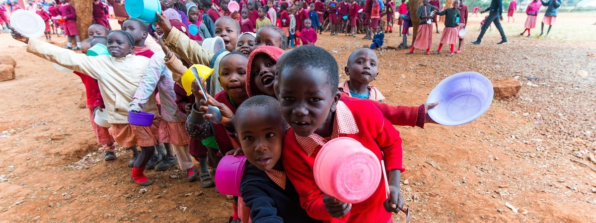 A large group of African school children wearing red uniforms gather with bowls outstretched