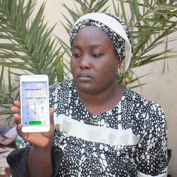 An African woman shows her phone with her Matontine savings numbers displayed