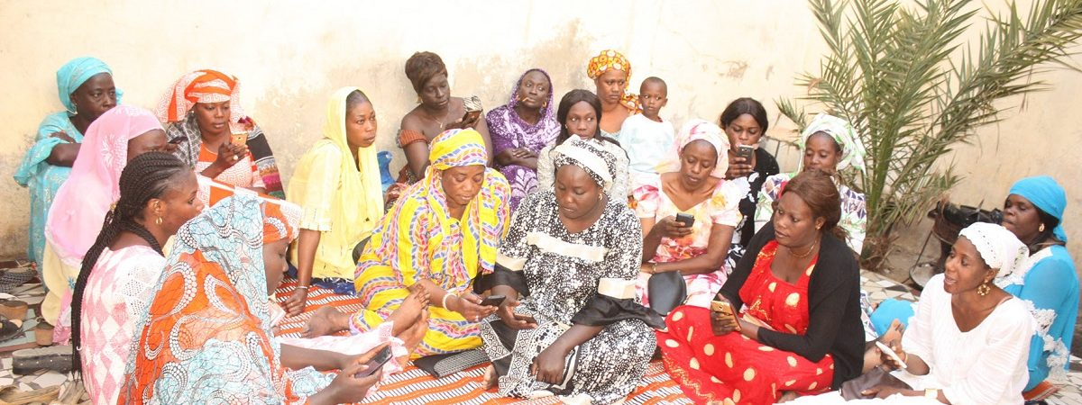 A large group of African women gather on a colorful rug and are using their mobile devices to check their savings to the MaTontine platform