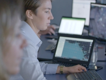 A fmember of the OceanMind team sits in a field office tracking data on multiple computer screens in front of her