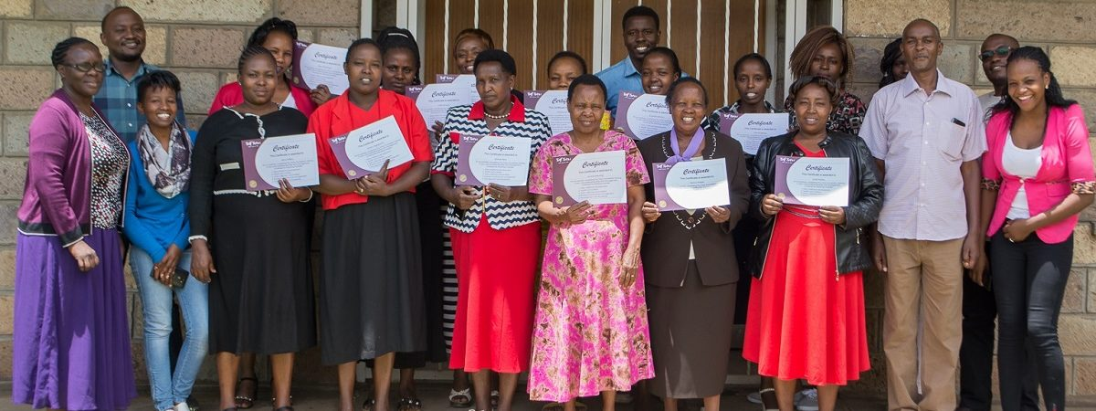 More than a dozen African women stand smiling and proudly holding their certificates