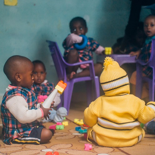 African children in daycare play on the floor with toys