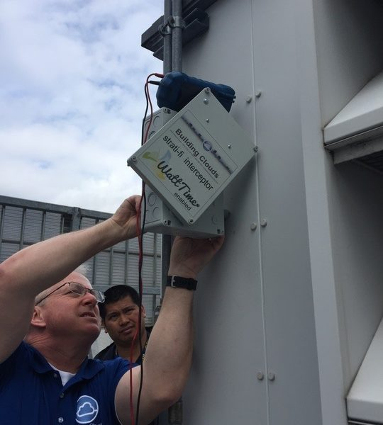 Two men install a WattTime device on an HVAC system