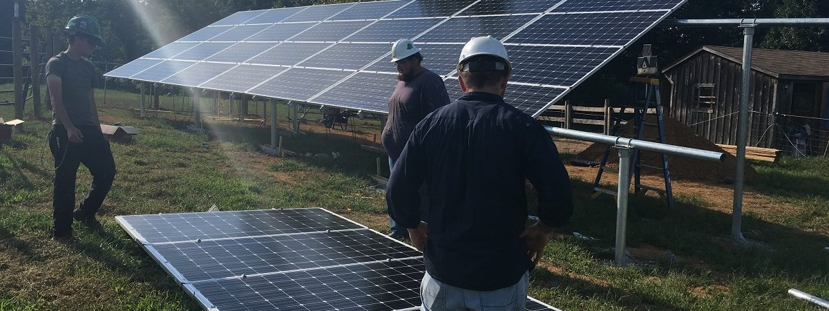 Three men install solar power panels in the sunshine