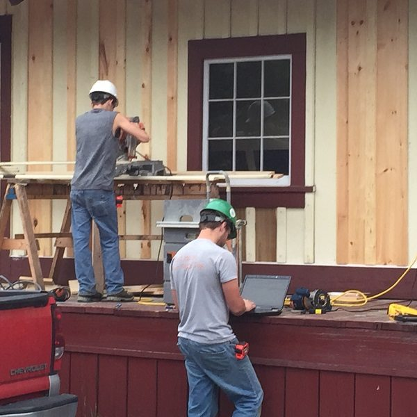 Two men in hard hats are featured; one is working to cut wood to install siding on the side of a house, while the other is using a laptop to look up parameters for the siding