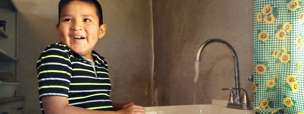 A Native America boy smiles as he washes his hands in his sink with clean flowing water