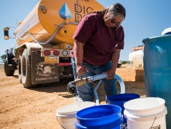 A native american woman fills buckets with clean water. The water is coming from a yellow DIGDEEP water truck.
