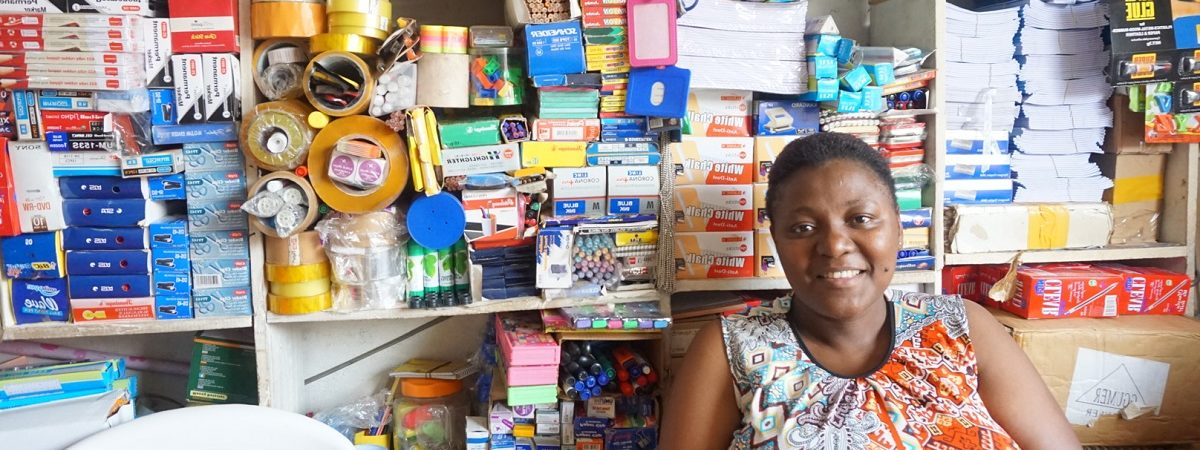 An African female small business owner sits inside of her store front
