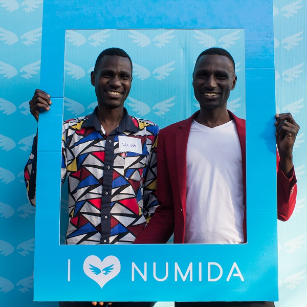 Two African men smile holding a card